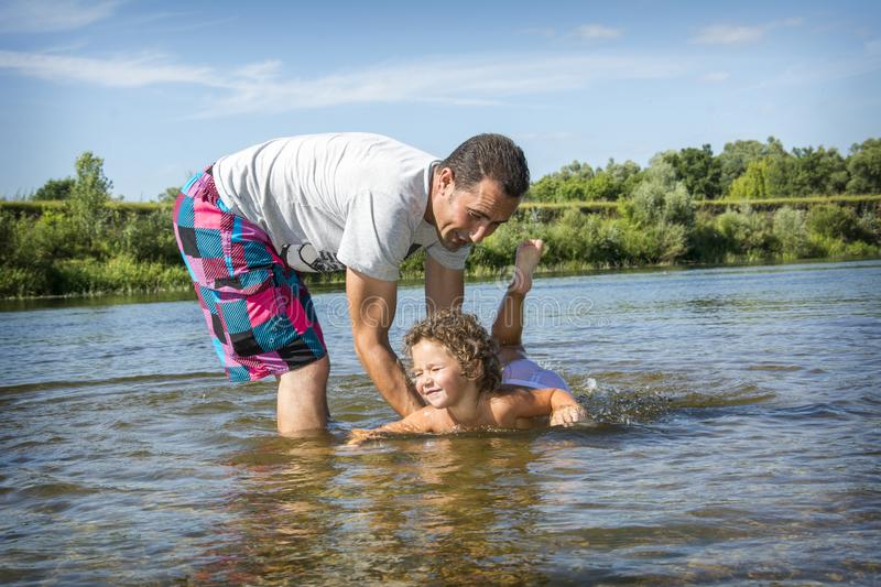 In the summer on the river, the father holds a small daughter in stock images