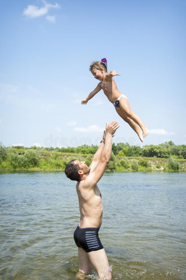 In summer, on the river, the father throws a little happy daughter up. stock photos