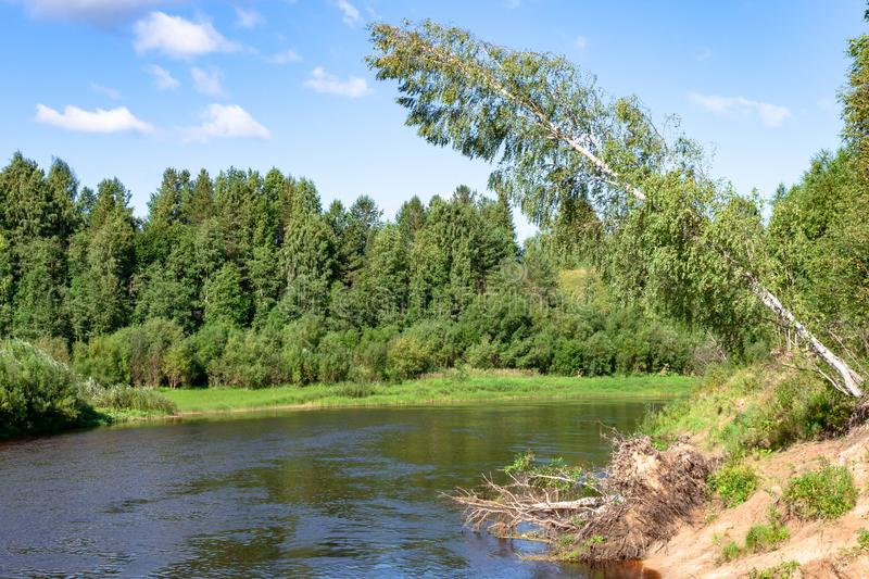 Summer river shore landscape. Sandy beach on banks, green grass and trees, blue river and cloudy sky stock photo