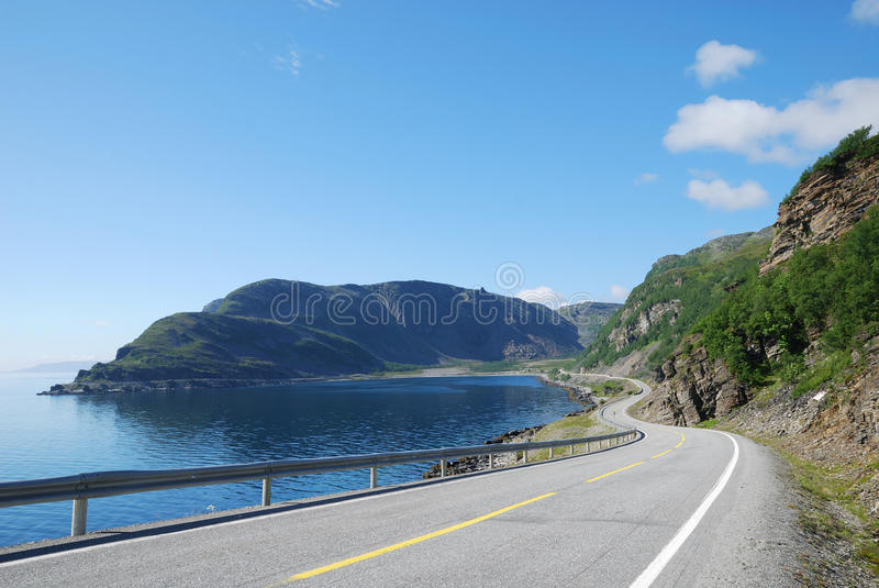 Summer road along the coast of Mageroya. Asphalt road is meandering between blue fjord and moss mountains. Highway is photographed with diminishing perspective stock images