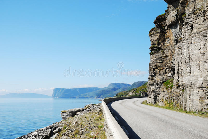 Summer road along the coast of Mageroya. Asphalt road is meandering between blue fjord and cliff. Mageroya is an island in Finnmark county in the extreme north royalty free stock images