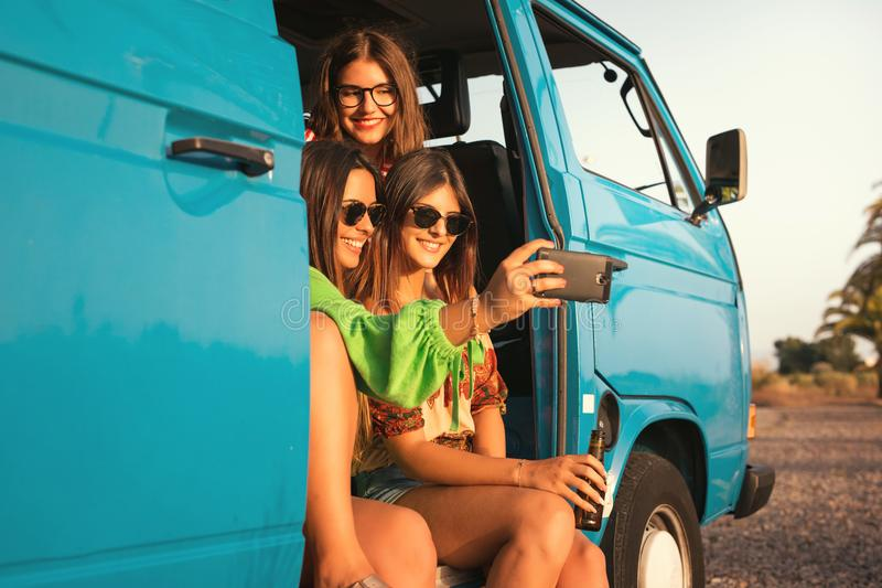 Summer Road-Trip. Summer holidays, road trip, vacation, travel and people concept - smiling young hippie women in car royalty free stock photography