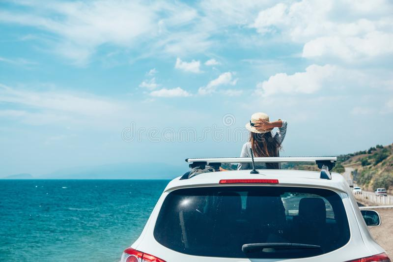 Summer roadtrip to the beach. Rear view of pre teen child in car over sea view on summer roadtrip to the beach stock photo