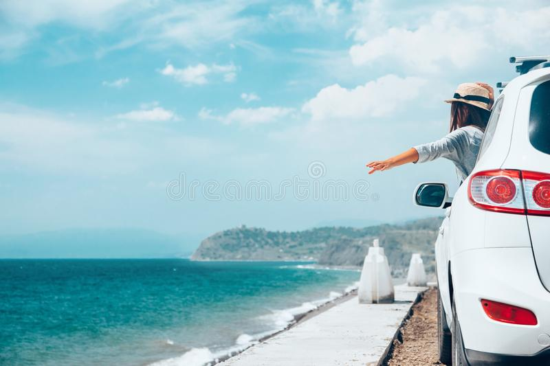 Summer roadtrip to the beach. Rear view of pre teen child in car over sea view on summer roadtrip to the beach stock photography