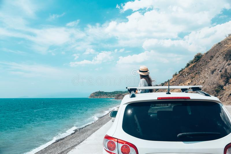 Summer roadtrip to the beach. Rear view of pre teen child in car over sea view on summer roadtrip to the beach royalty free stock images