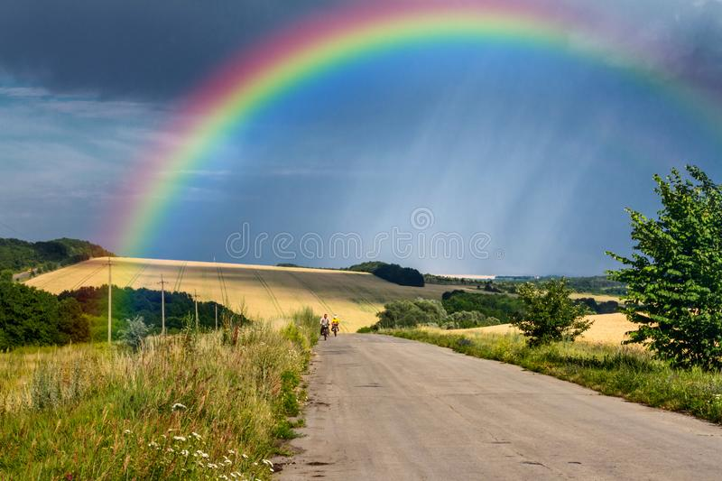 Summer rural landscape - road with cyclists in the rays of the setting sun on background distant rainbow. Summer rural landscape - road with cyclists in the rays royalty free stock photos