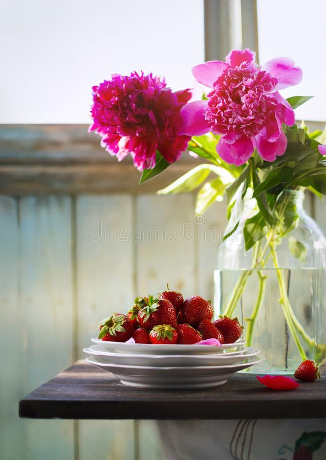 Summer rustic still life with strawberry and peony bouquet royalty free stock image