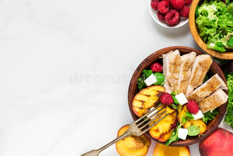 Summer salad with grilled chicken and peach, feta cheese and raspberries in a bowl with fork. healthy food. top view. With copy space royalty free stock image