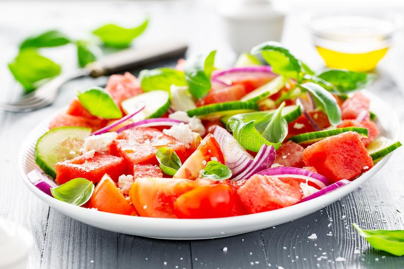 Summer salad with watermelon and salad leaves. Tasty summer refreshing watermelon salad with salad leaves, basil, feta and olive oil. Served on plate on table royalty free stock photo