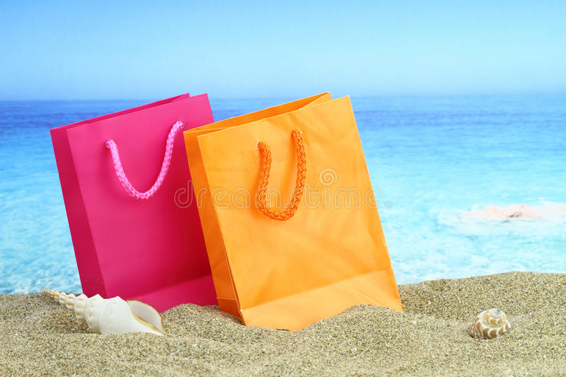Summer sale. Shopping bags on the sand stock photo