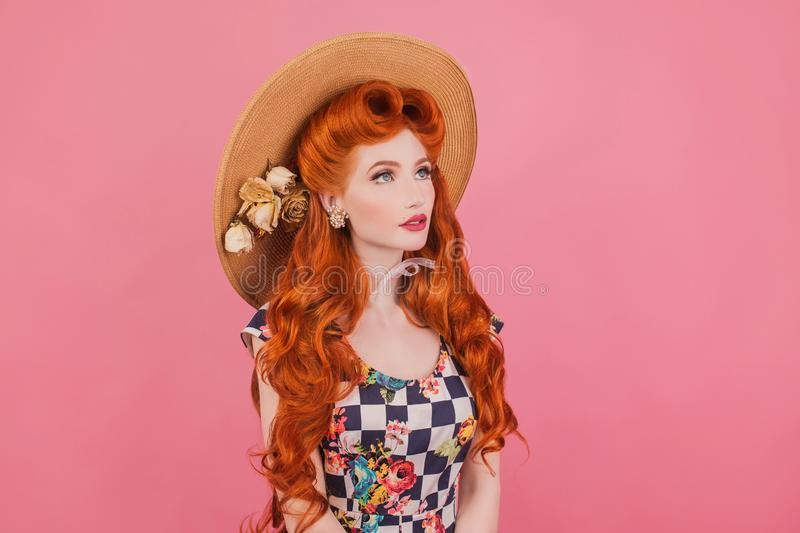 Summer sale concept. Beautiful stylish outfit. Amazed redhead model with vintage hairstyle in hat on pastel pink background. stock images