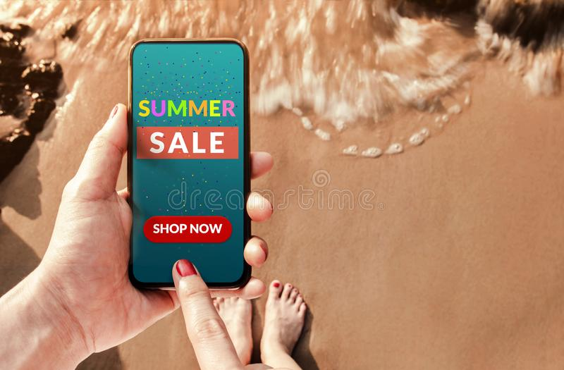 Summer Sale Promotional Concept. Top view of Woman Customer using Smart Phone with Advertising Deals on the Screen at Summer royalty free stock photography