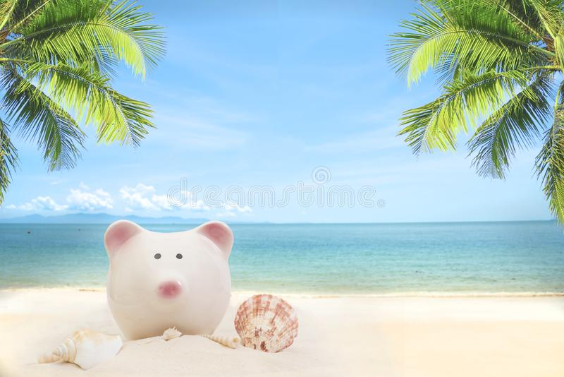 Summer sandy beach with piggy bank and coconut tree stock photos