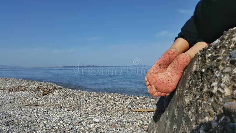 Summer scene and feet on the rock royalty free stock image