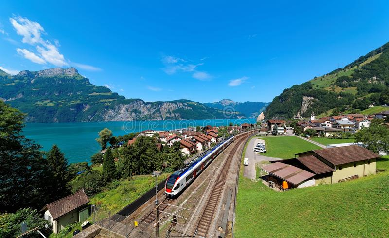 Summer scenery of beautiful Lake Lucerne on a sunny day, with a train traveling on the railway thru Sisikon Village royalty free stock image