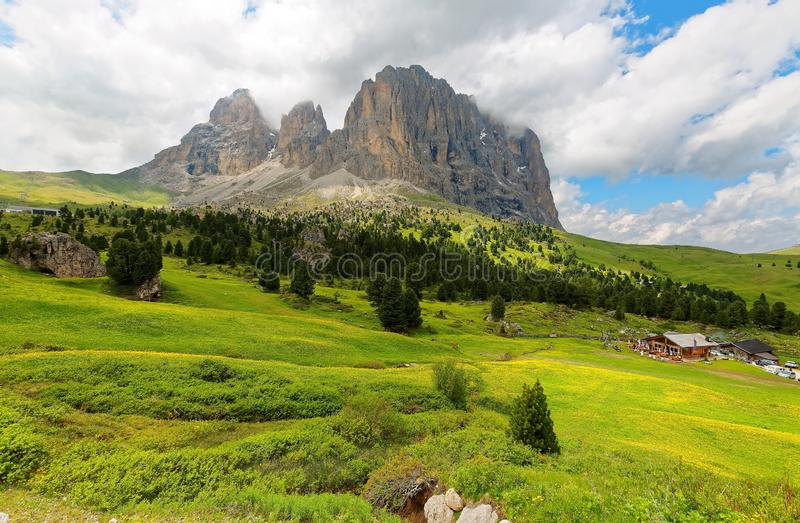 Summer scenery of rugged Alpine mountains with view of rocky Sassolungo-Sassopiatto. Langkofel-Plattkofel  and grassy fields under cloudy sky in Val Gardena royalty free stock image