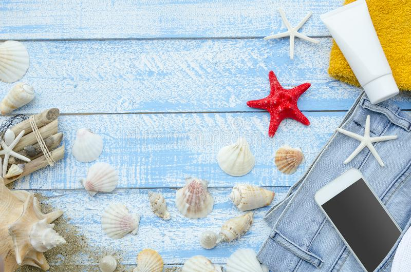 Summer sea beach concept. Top view blue wooden planks with seashells, rocks, sand and sunblock cream. White phone with royalty free stock photography