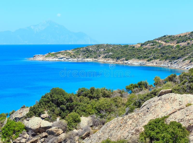 Summer sea coast Halkidiki, Greece. Summer sea scenery with aquamarine transparent water and Athos Mount. View from shore Sithonia, Halkidiki, Greece royalty free stock image