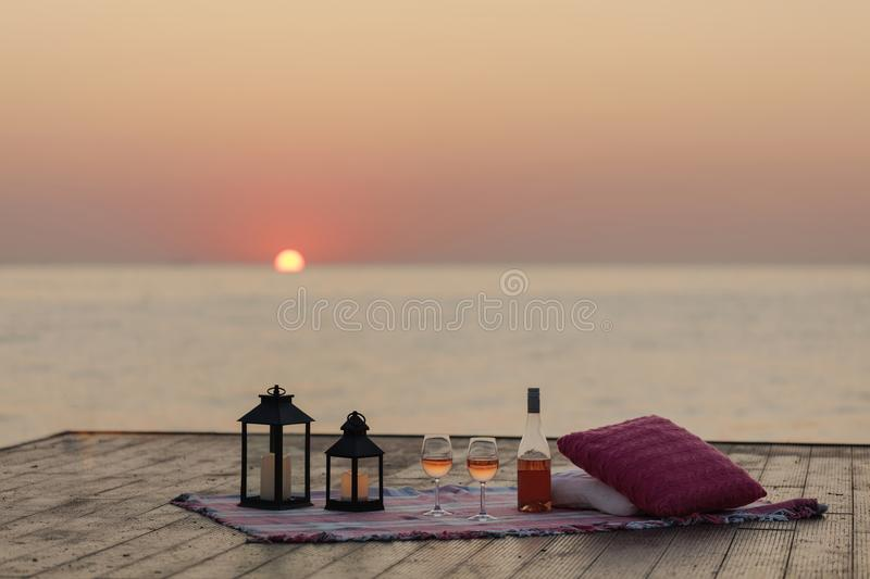 Summer sea sunset. Romantic picnic on the beach. Bottle of wine, glasses, candles, plaid and pillows. royalty free stock images