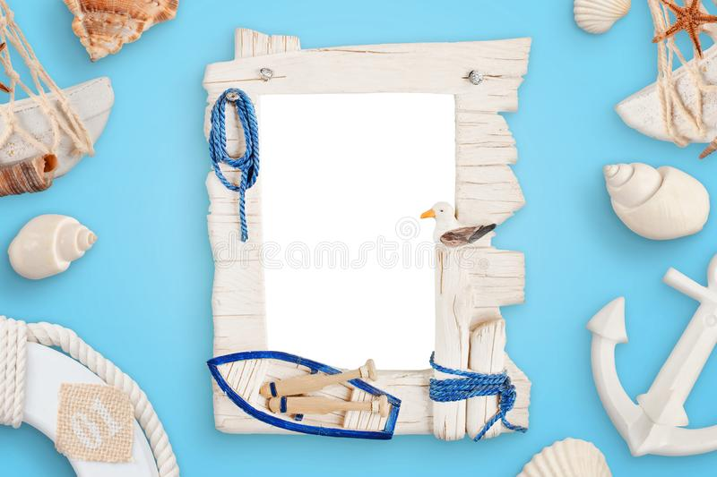 Summer sea travel photo frame on blue desk surrounded with shells, boat anchor, lifebelt.  stock photography