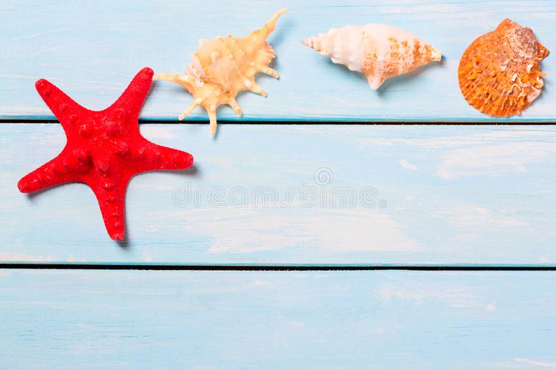 Summer sea vacation background with shells and red star on a wooden blue background with copy space royalty free stock photo