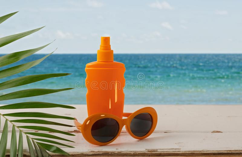 Summer seascape. Relax on the beach, sunblock, hat and orange sunglasses. royalty free stock image