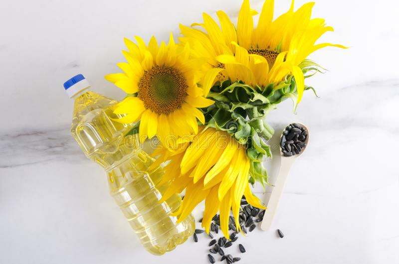 Summer season and blooming sunflowers.Plastic bottle of sunflower oil and seeds on the white surface, top view. Wooden spoon of seeds, sunflowers and bottke of royalty free stock photos