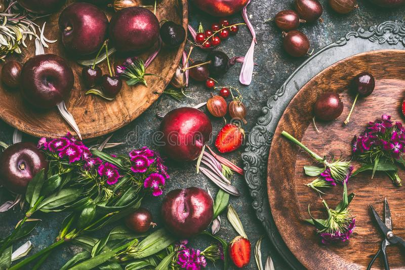 Summer seasonal fruits and berries with garden flowers in plates on dark rustic background. Top view royalty free stock image