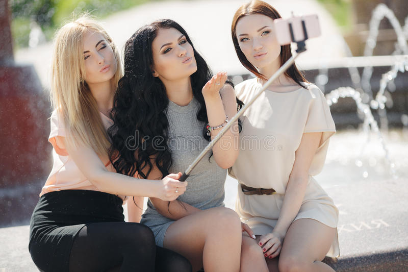 The summer selfie of three friends in the Park near the fountain royalty free stock image