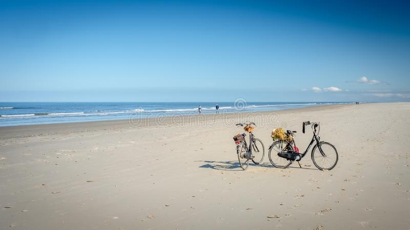 Two bikes on the Schiermonnikoog beach waiting for their owners stock images