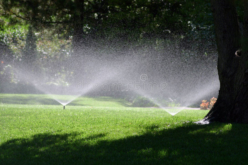 Summer Shower. A photograph of a water sprinkler showering flowers during a hot summer July day in Oklahoma City stock photos