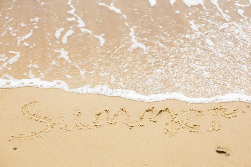Summer sign on beach. Written summer text word on sandy beach  and sea waves with foam. Hello summer concept. Top view. Vacation, stock photography