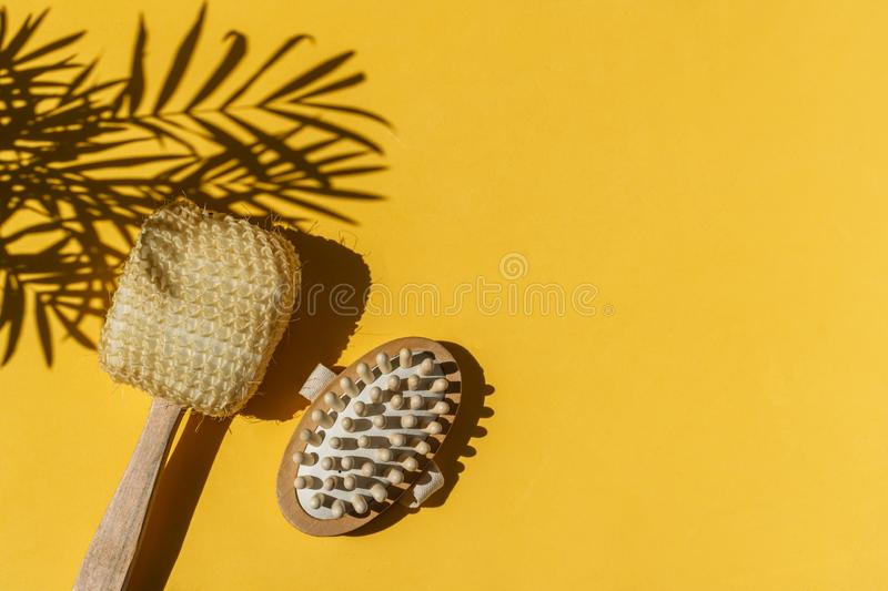 Shower sponge with wooden handle, anti cellulite massager on bright yellow background royalty free stock photo