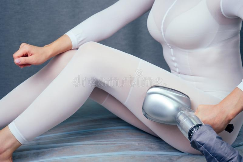 Summer slimming body care season concept.beauty woman in white sexy suit getting apparatus massage for thinness buttocks stock photo