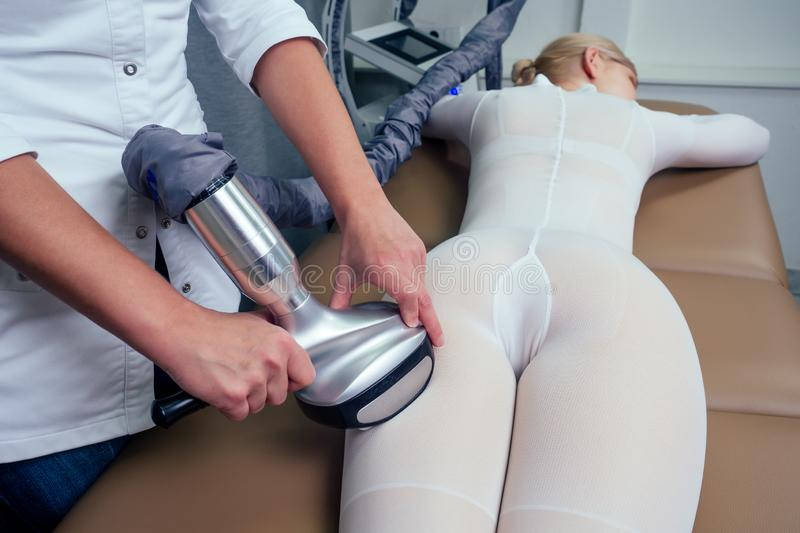 Summer slimming body care season concept.beauty woman in white sexy suit getting apparatus massage for thinness buttocks. Waist . medical cosmetologist royalty free stock image