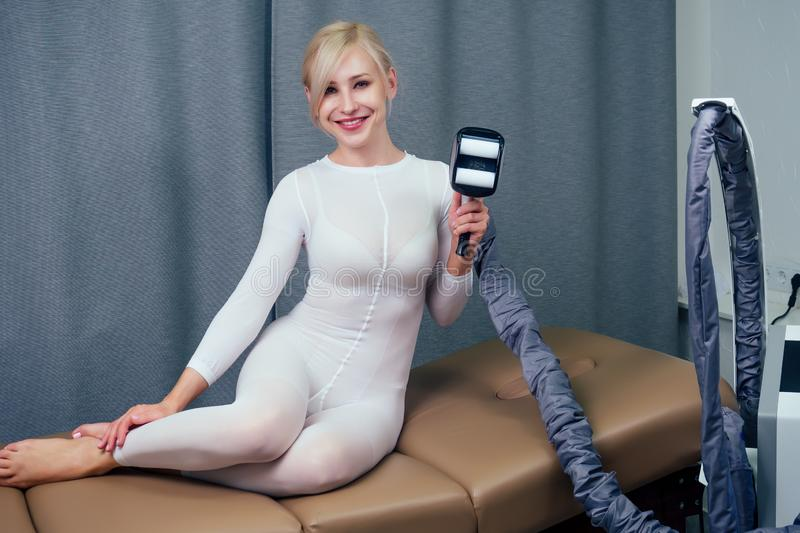 Summer slimming body care season concept.beauty woman in white sexy suit getting apparatus massage for thinness buttocks. Waist . medical cosmetologist royalty free stock photo