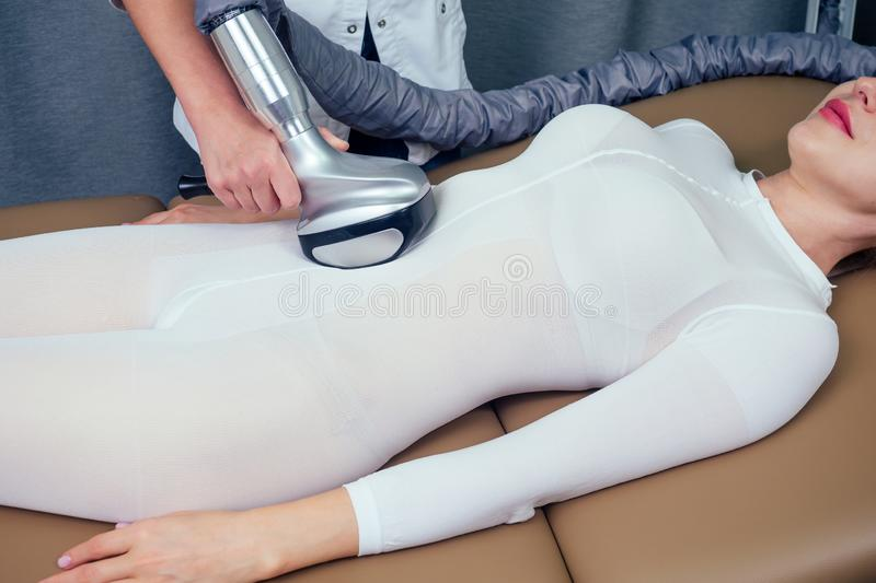 Summer slimming body care season concept.beauty woman in white sexy suit getting apparatus massage for thinness stomach. Waist . medical cosmetologist royalty free stock images