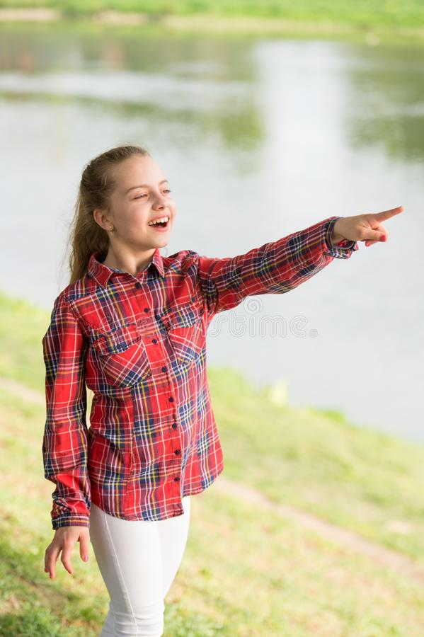 Always summer. Small girl pointing finger at river on summer landscape. Adorable child with long blond hair in casual. Plaid style on summer vacation. Little stock photo