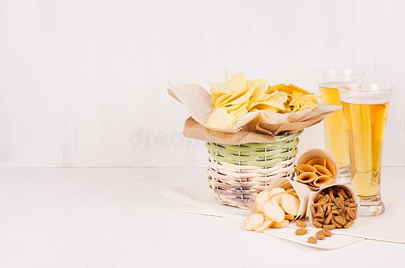 Summer snacks and lager beer in glass - nachos, croutons, chips, tortilla in rustic basket and paper corners on white wood backgr. Ound royalty free stock image
