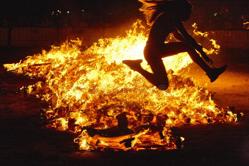 Summer solstice celebration in Spain. Woman jump. Fire flames. Horizontal stock photography