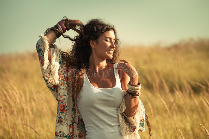 Summer spirit. Smiling young woman wearing boho style clothes enjoy in summer day on the field of grass, retro colors royalty free stock image