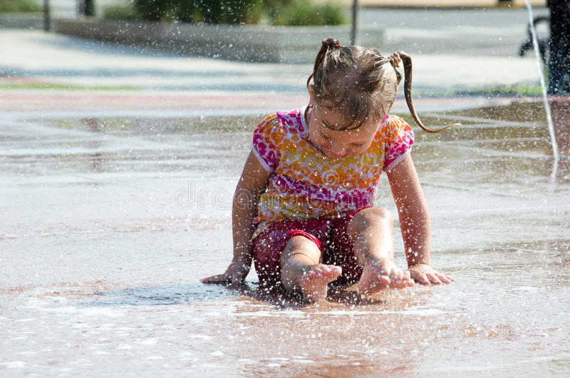 Summer splash. A small girl splashes happily in a city park, where there are fountains and sprinklers for summer kids delight royalty free stock photography