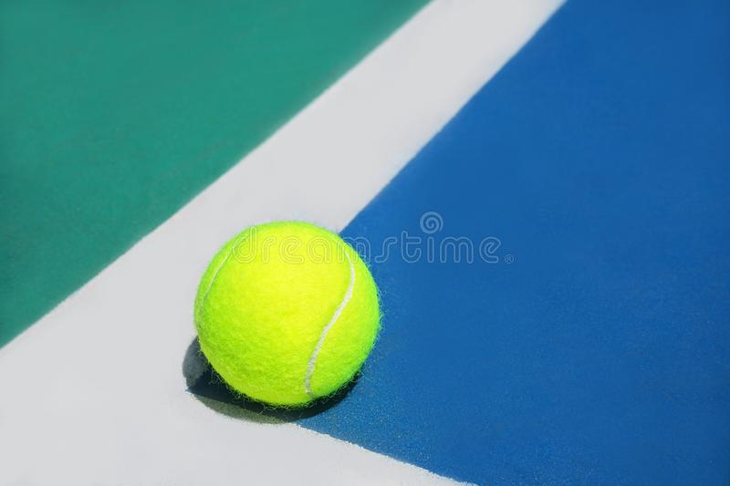 Summer sport concept with tennis ball on white line in the corner of hard tennis court royalty free stock photography