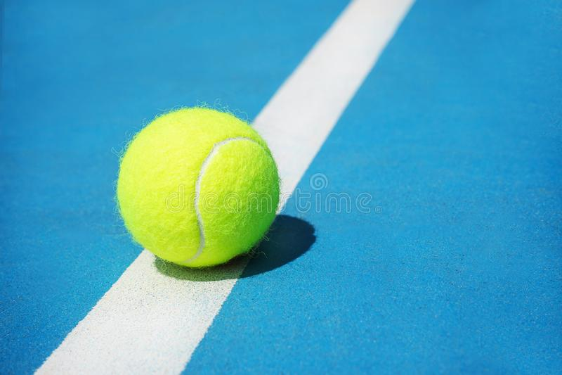 Summer sport concept with tennis ball on white line on hard tennis court stock photography