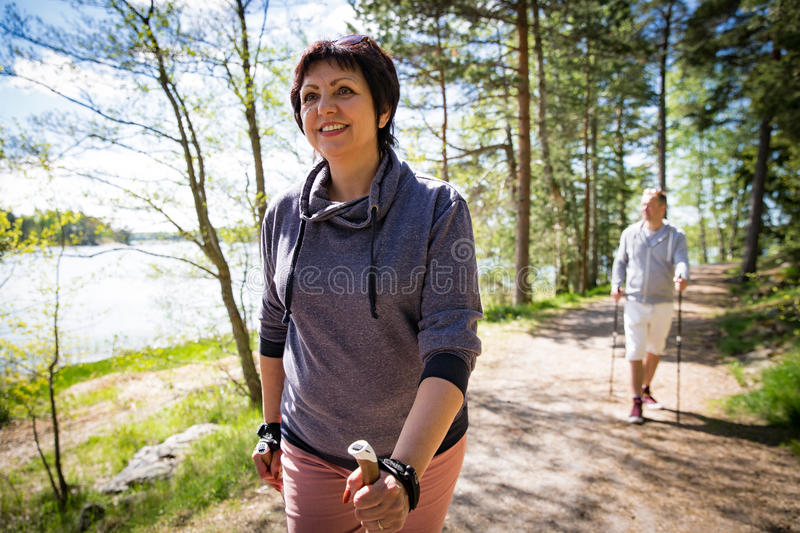Summer sport in Finland - nordic walking. Man and mature women hiking in green sunny forest. Active people outdoors. Scenic peaceful Finnish summer landscape stock image