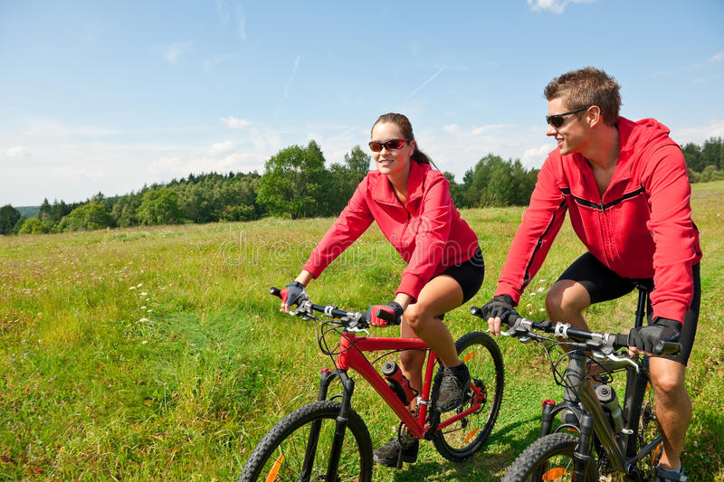 Download Summer - Sportive Couple Riding Bike In Meadow Stock Image - Image: 10915351