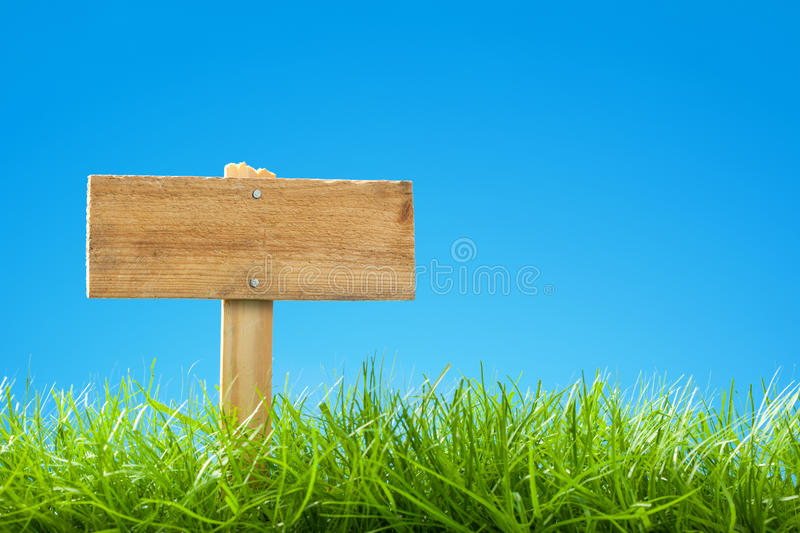 Summer / Spring Scene with Green Grass and Clear Blue Sky - Empty Wooden Sign Post stock photography