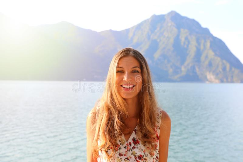 Summer / spring woman smiling happy with flowery dress in sunny. Day on lake. Beautiful cheerful attractive girl outdoor royalty free stock photography