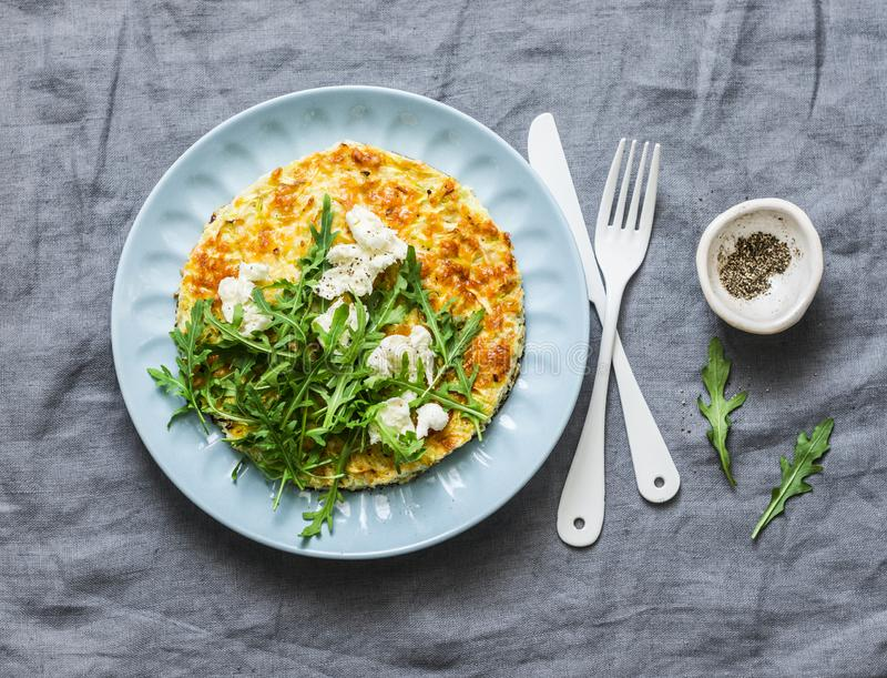 Summer squash frittata with goat cheese and arugula - delicious healthy diet food, breakfast, snack on a gray background. Top view stock photography