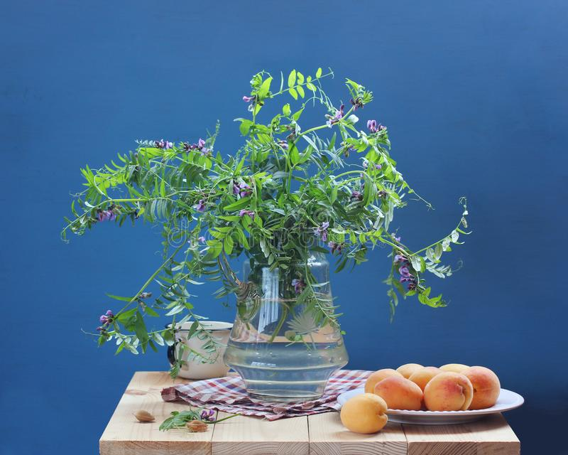Summer still life with flowers and fruit on a blue background stock images